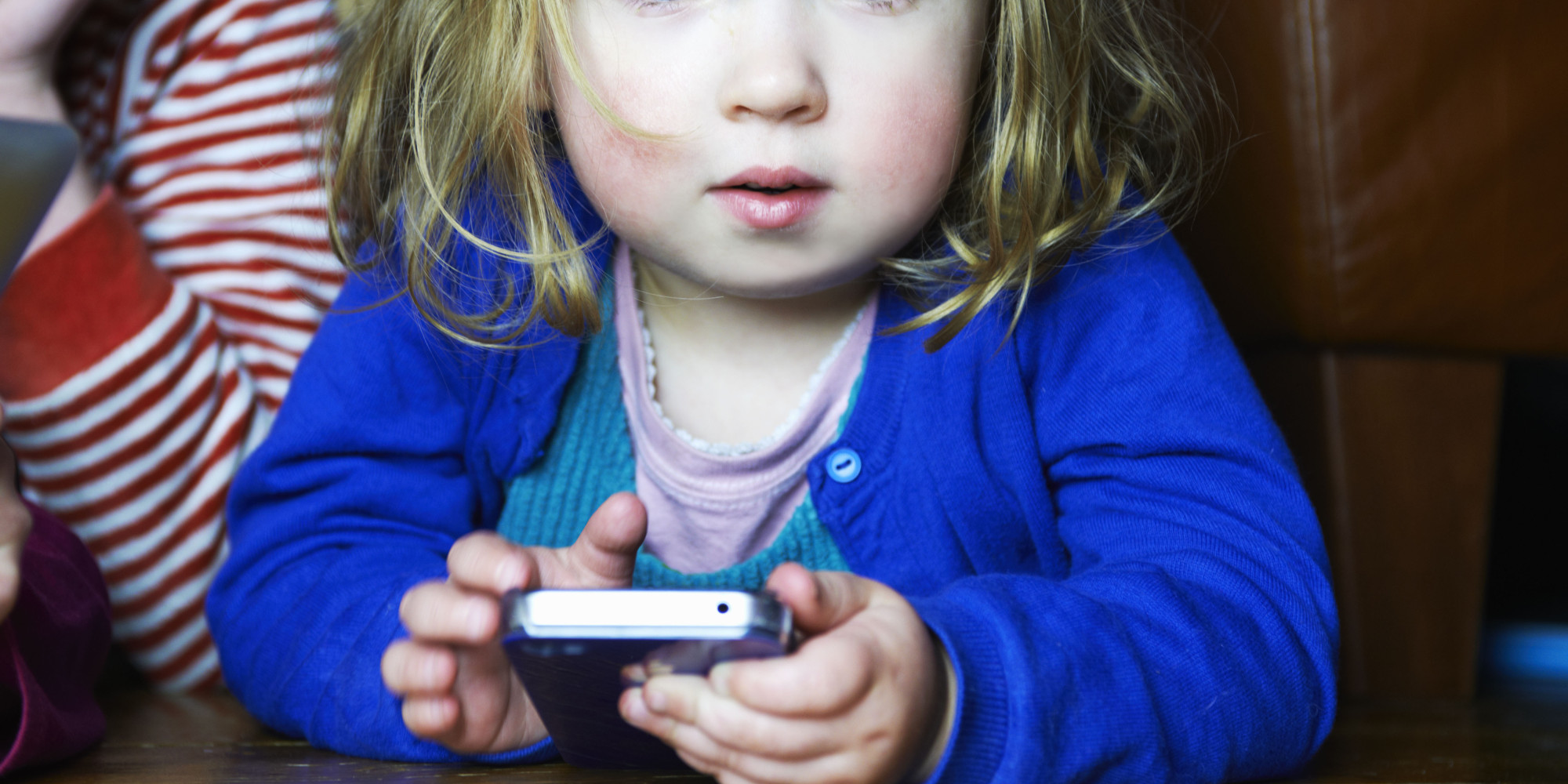 young girl holding mobile phone looking to camera